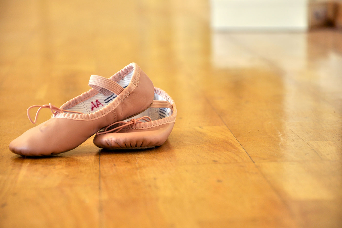 A pair of dance slippers set up on the dance floor.