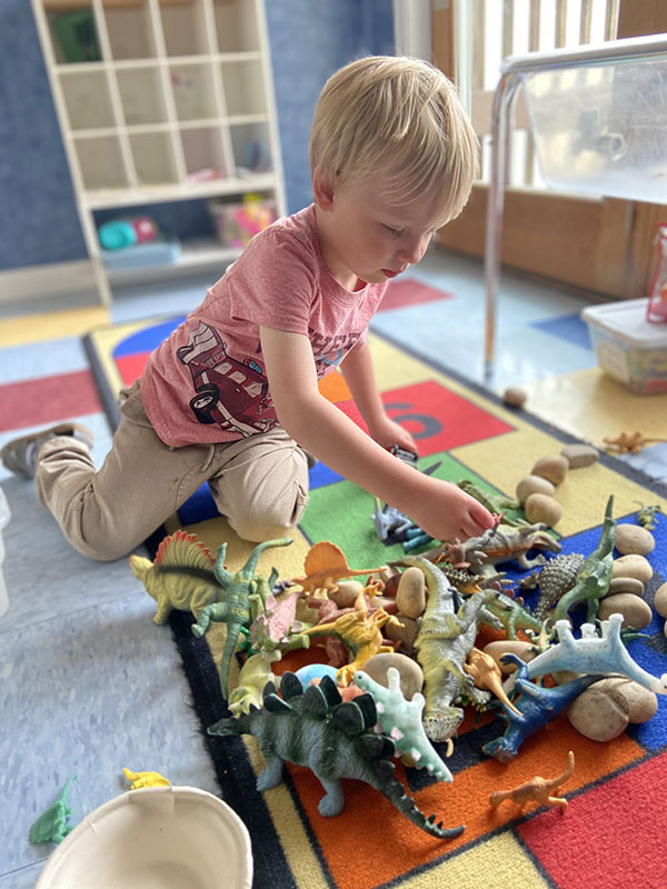 Child playing with a collection of toy dinosaurs inside the Discovery School.