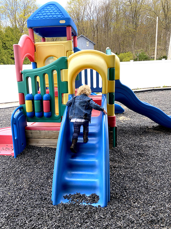 Young child climbing up stairs on an outdoor plastic playhouse.