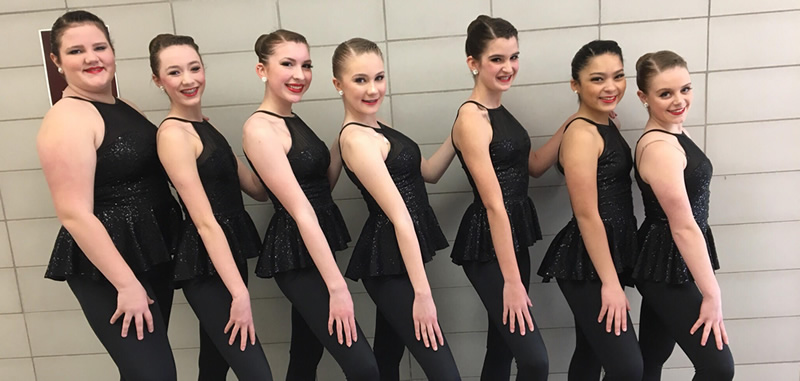 Young women wearing black dance uniforms, lined up and smiling at camera.