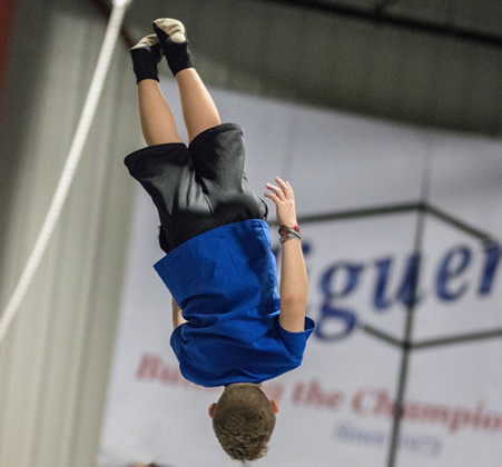 A kid flipping upside down in the air after bounding from a trampoline.