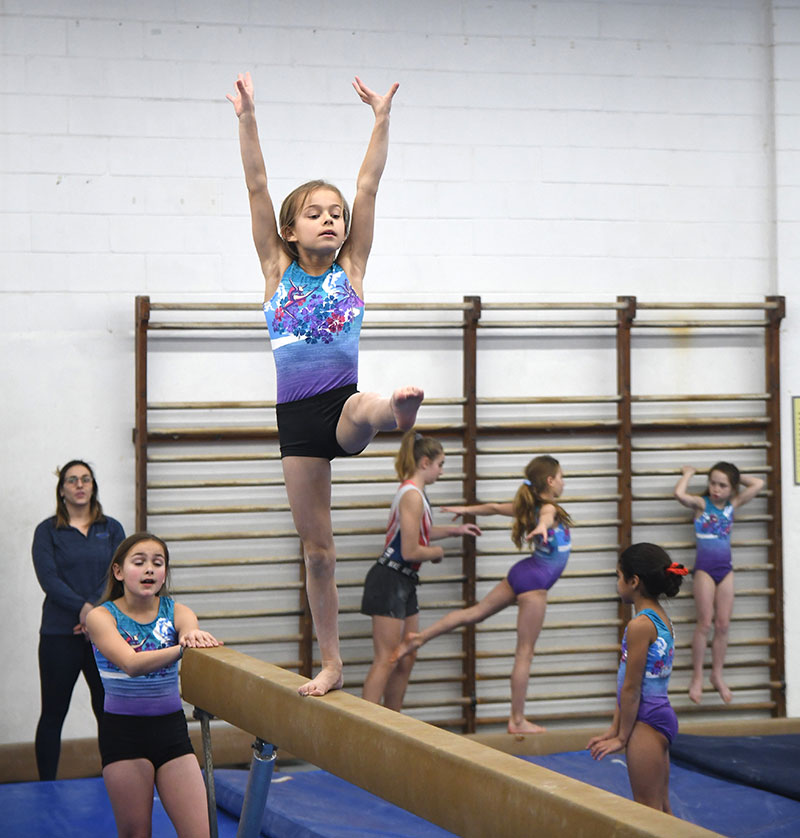 Child performing on a balance beam while their peers and coach look on.