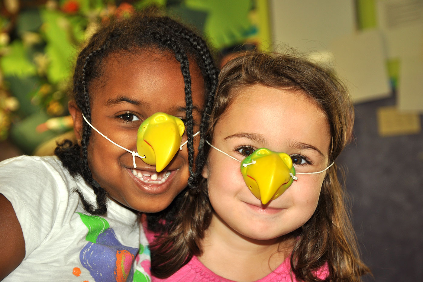 Two young children smiling together while wearing bird beak masks that cover their noses.