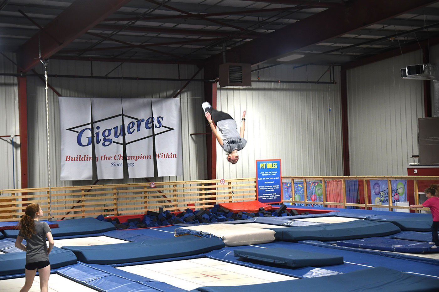 Gymnast photographed mid-air during an acromatic maneuver.