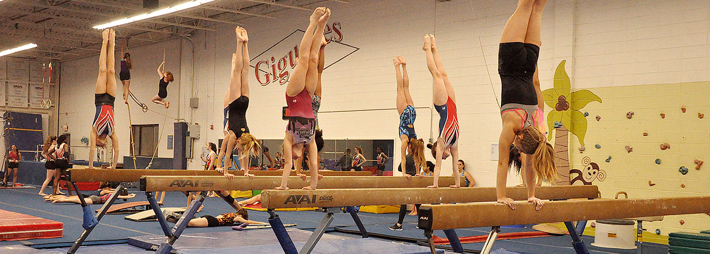 Group of young adults performing handstands on balance beams during classes.