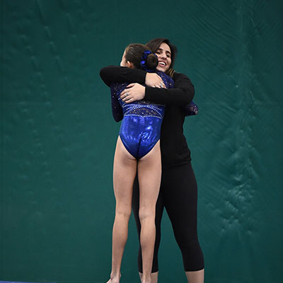 Junior Staff Director Kenar Charchaflian hugging a gymnastic student.