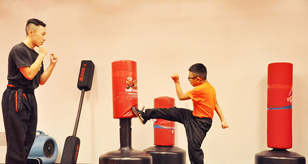 Children practicing Kung Fu with dummy and instructor.