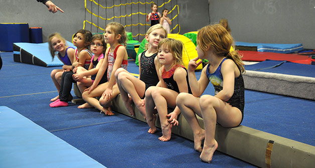 Lineup of young children sitting down on a balance beam in gym outfits.
