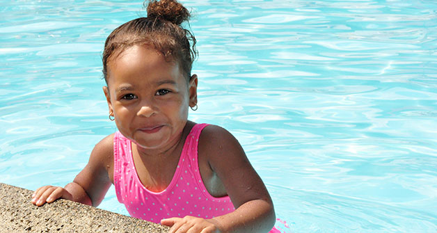 Headshot of smiling child at the edge of a pool in summer.